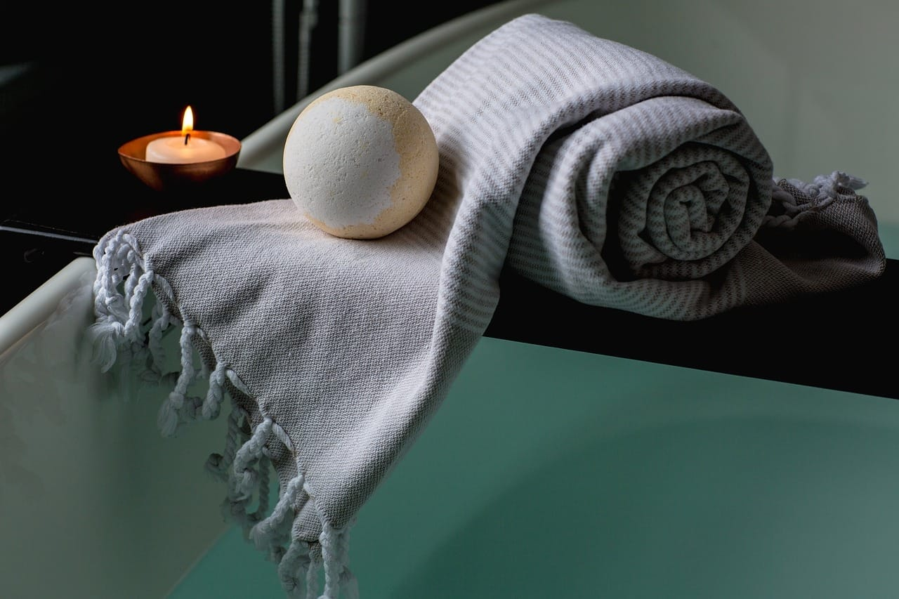 Bath Bomb And Candle Resting On A Towel By The Bath