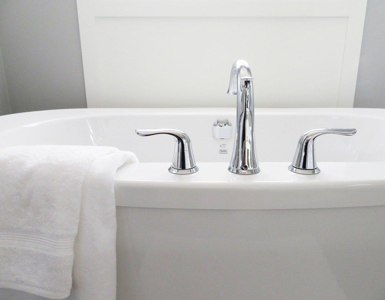 White Towel Draped Over Clean, White Bathub