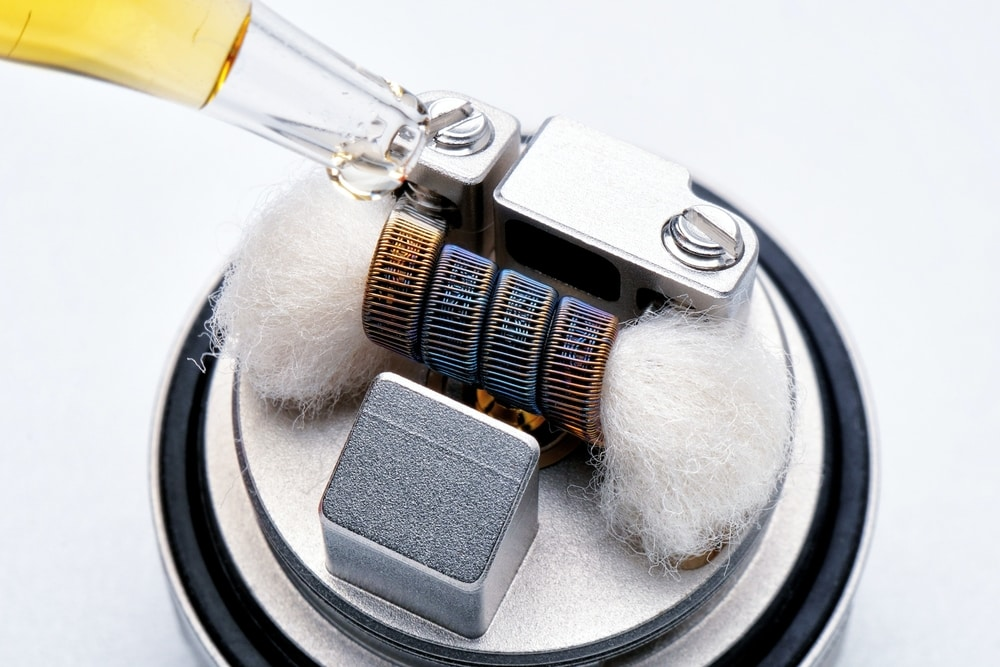 CBD vape juice dropping onto vaporizer coils