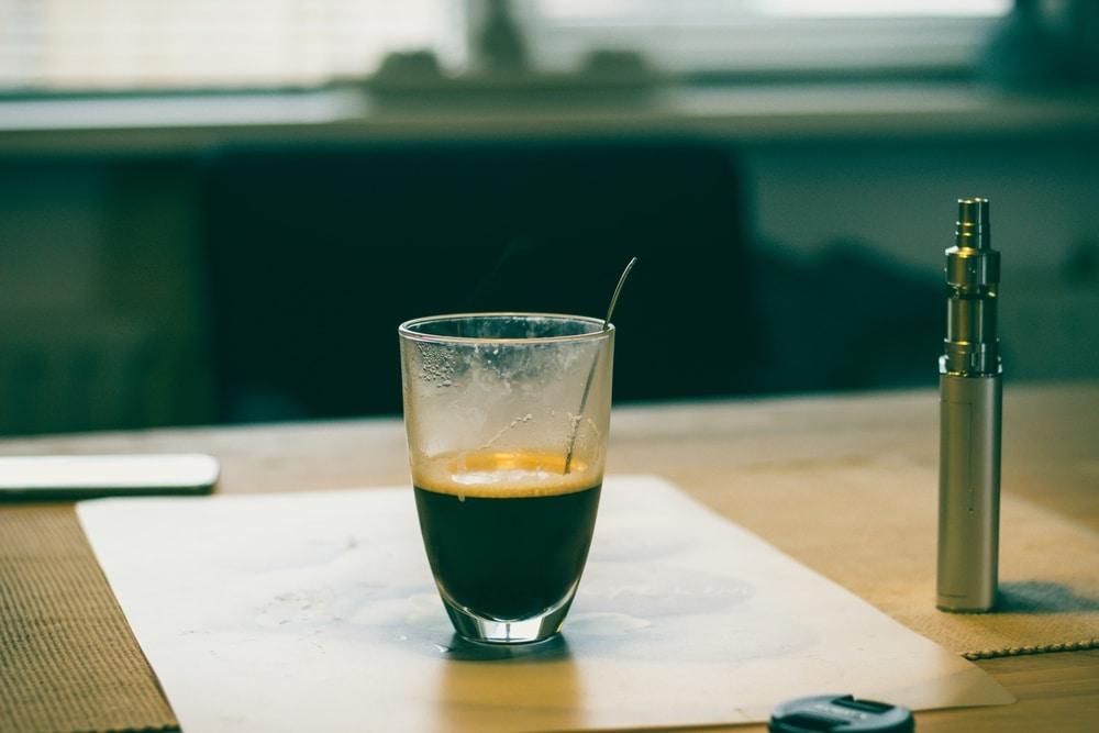 CBD vape pen standing next to a cup of coffee