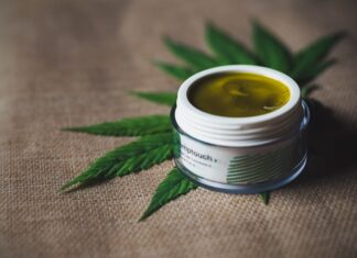 CBD topical balm on a hemp leaf